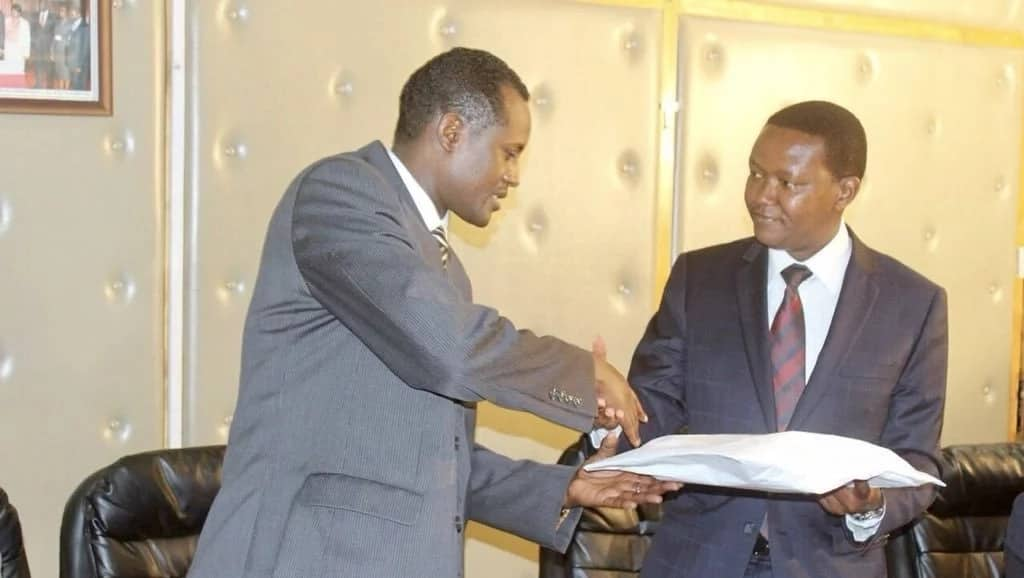 Machakos County Governor Alfred Mutual handing over details of his bank accounts and properties to the EACC official.
