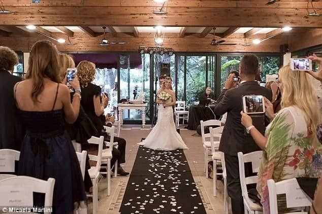 Walking down the aisle as guests applaud. Photo: Micaela Martini