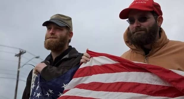 Two white supremacists are seen during their protest. Photo: REX