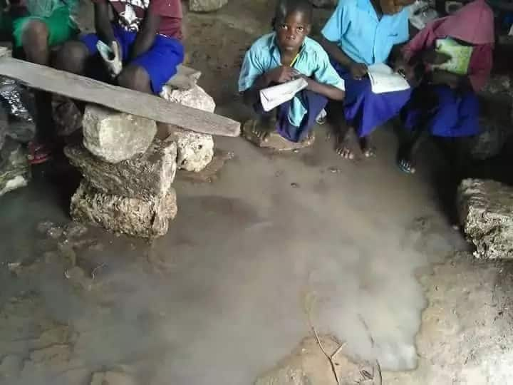 Pupils sitting on stones inside flooded classroom at Kianjogu Primary School in Laikipia County.