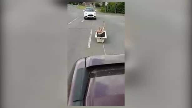 Unusual moment as man risks his life being towed in a bathtub behind car in busy highway
