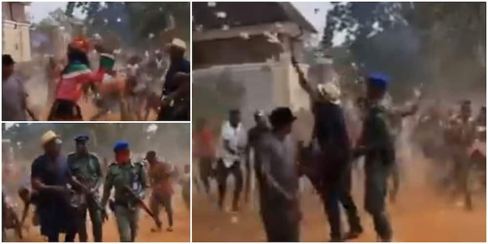 Reactions as masquerade, others jostle to pick cash as man sprays money on street.