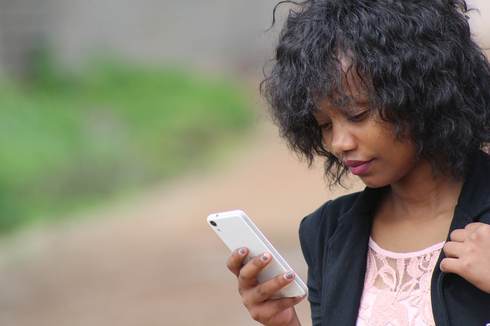 A woman looking at her phone. Photo: Relationshipsgalore.