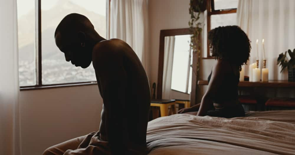 A couple sitting on bed after an argument.