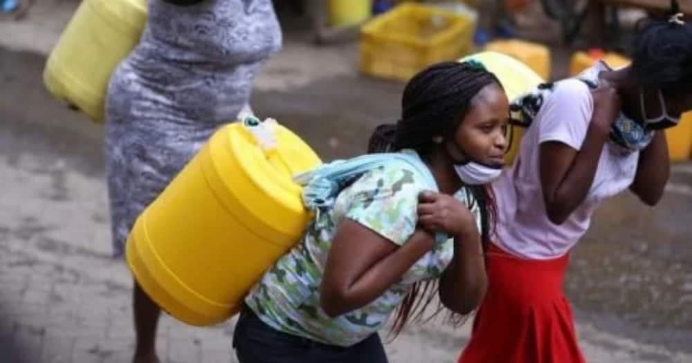 Women carrying water donated in Nairobi Mathare. Photo: Mike Sonko.