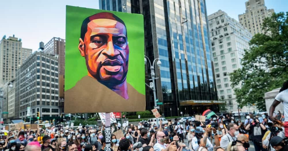 Hundreds of people pack into Columbus Circle to hear speeches against police violence while one of them holds a painted portrait of George Floyd in front of Trump International Hotel and Tower at Columbus Circle. Photo: Getty Images.