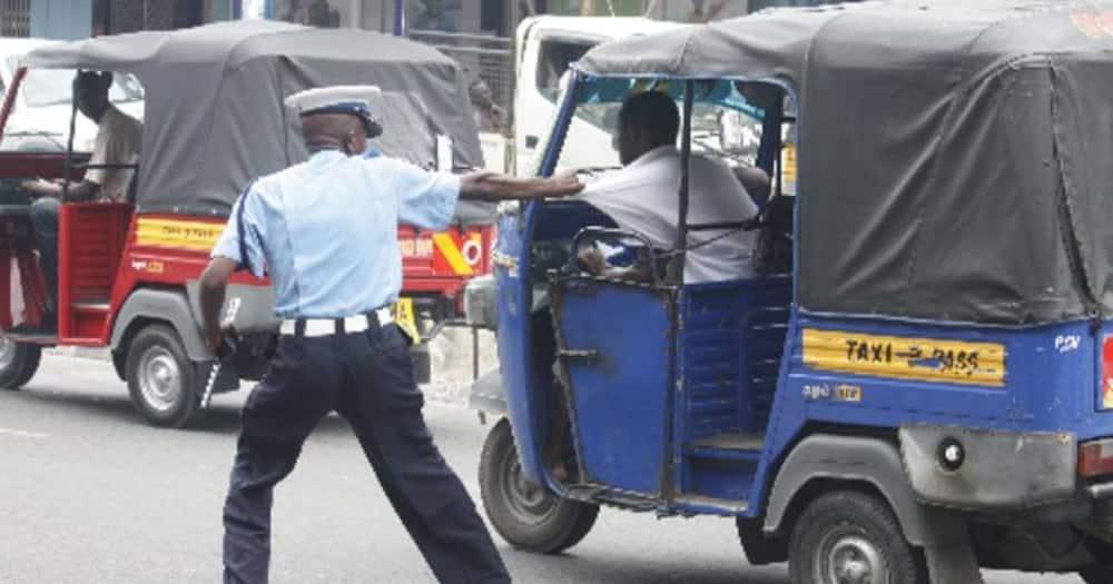 A police officer manhandling a Tuk Tuk driver. Photo: Road Alerts.