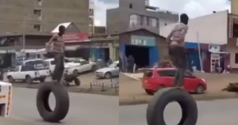 Daring Man Braves Dangerous Walk on a Large Tyre in a Busy Street