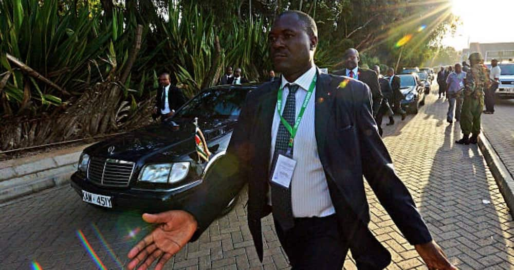 Uhuru is being driven in a Mercedes-Benz Pullman S600.