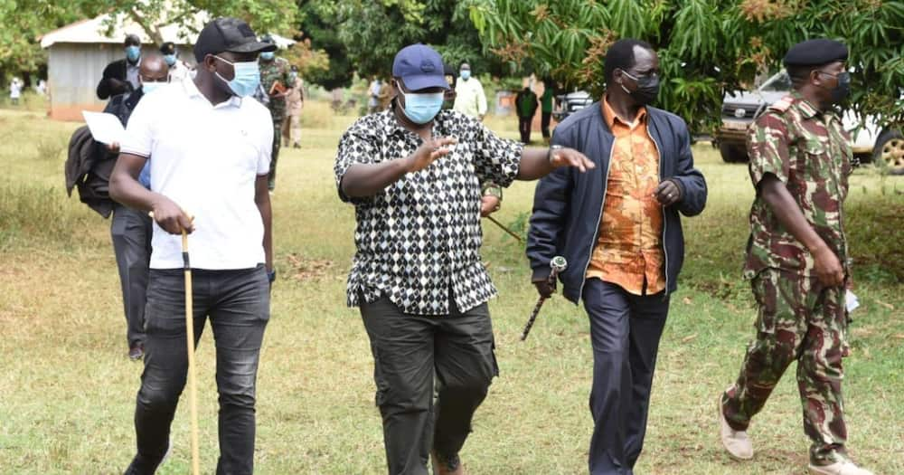 Kipchumba Murkomen (in white top) chats with Interior CS Fred Matiang'i (in blue cap).
