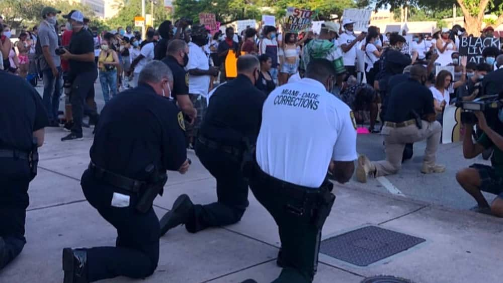 George Floyd: Solemn moment as police officers join protesters, kneel to pray