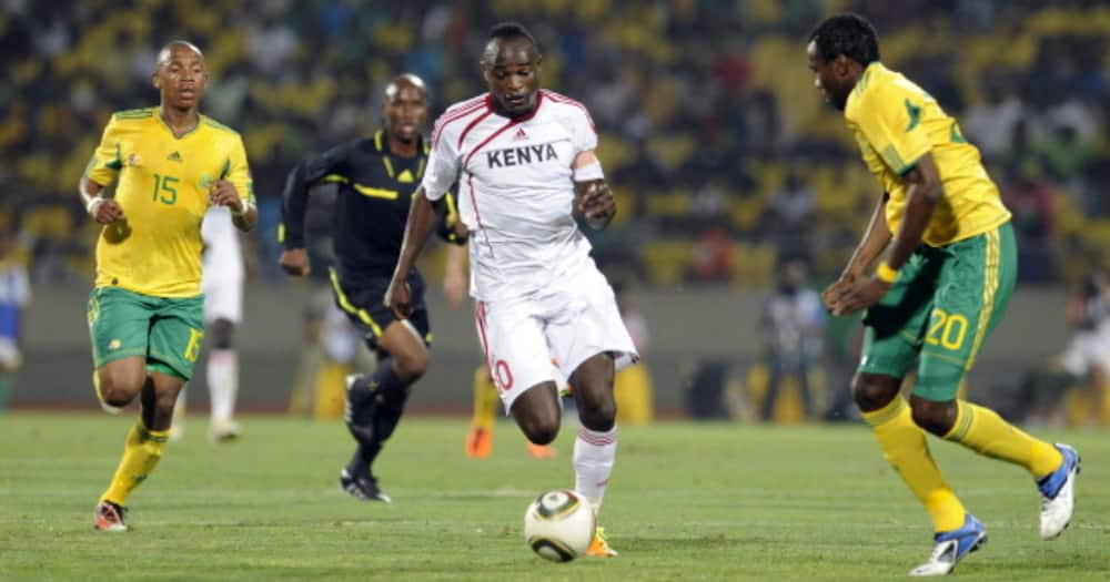 Dennis Oliech runs between South African players during the International friendly match between South Africa and Kenya at Royal Bafokeng Stadium on February 09, 2011 in Rustenburg, South Africa. (Photo by Lefty Shivambu/Gallo Images/Getty Images)