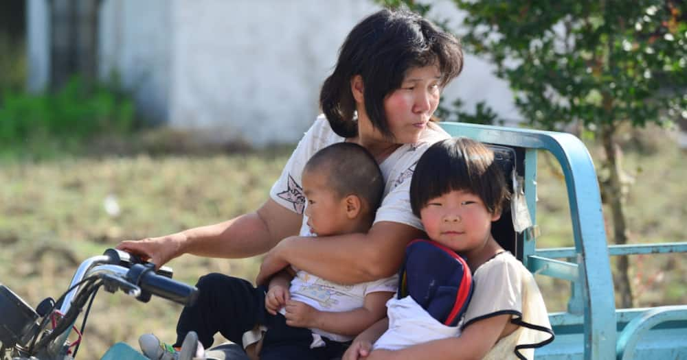 A woman picks up her children after school at a central kindergarten of lvzhai Town. Photo: Getty Images.