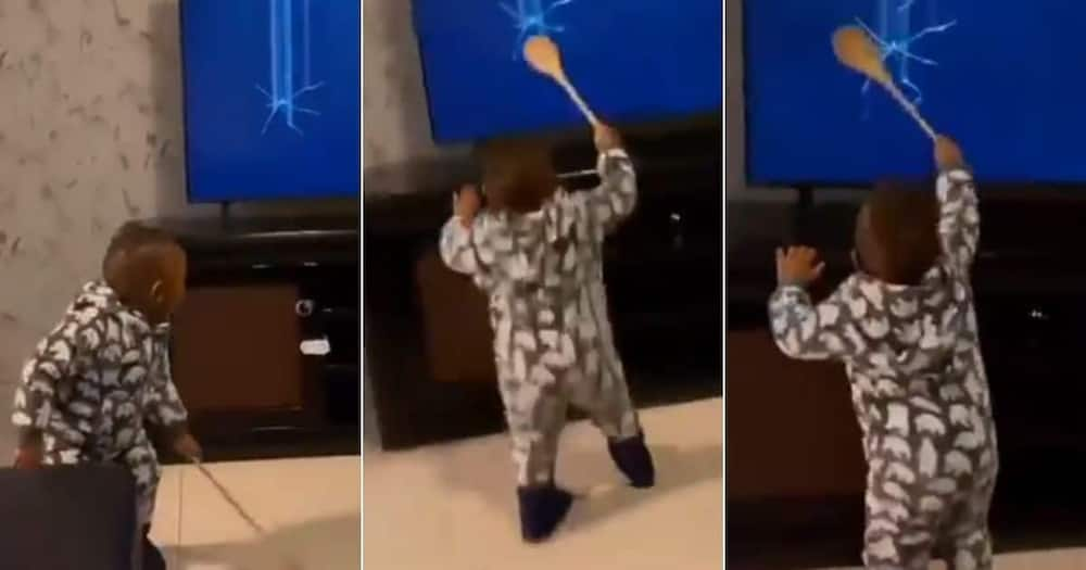 The toddler is seen smashing her mother's TV set.