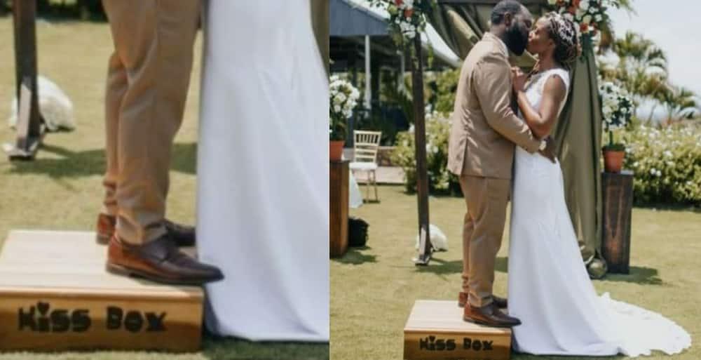 Groom stands on a platform to kiss taller bride.