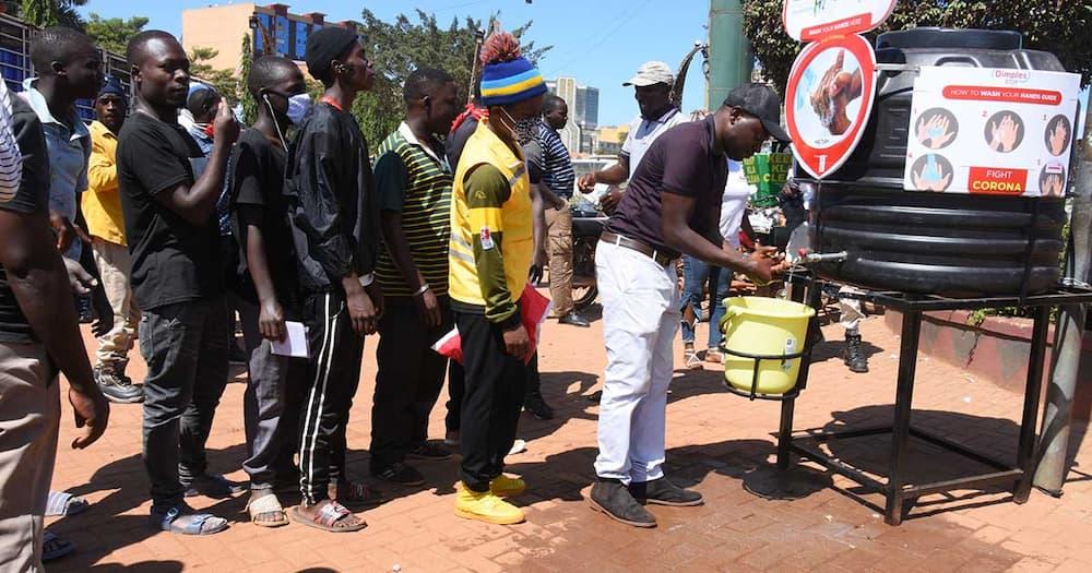 Farouk Mujumba (washing hands) is a Uganda-based businessman.
