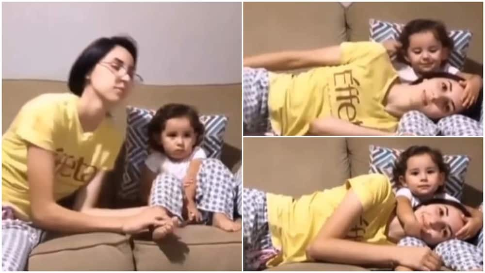 Beautiful moment mother rests on baby's legs, she pats her head in lovely way