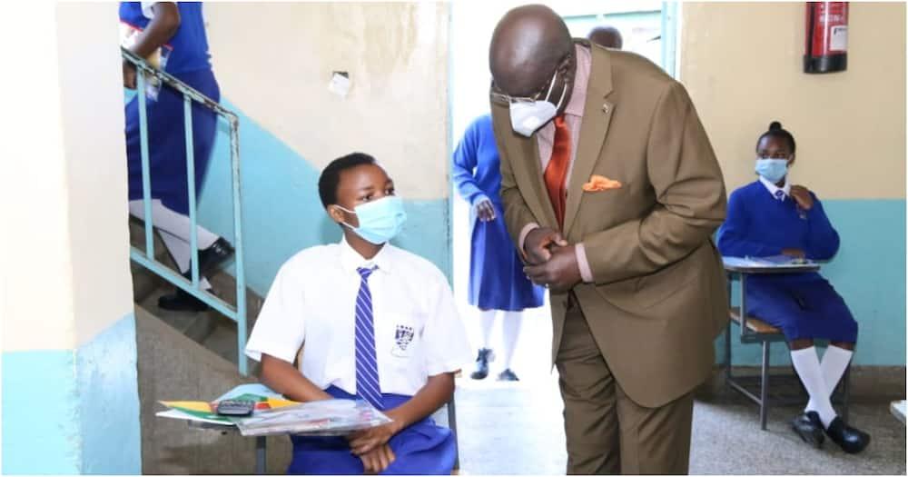 Education Cabinet Secretary George Magoha conversing with a KCSE candidate. Photo: EduMinKenya.