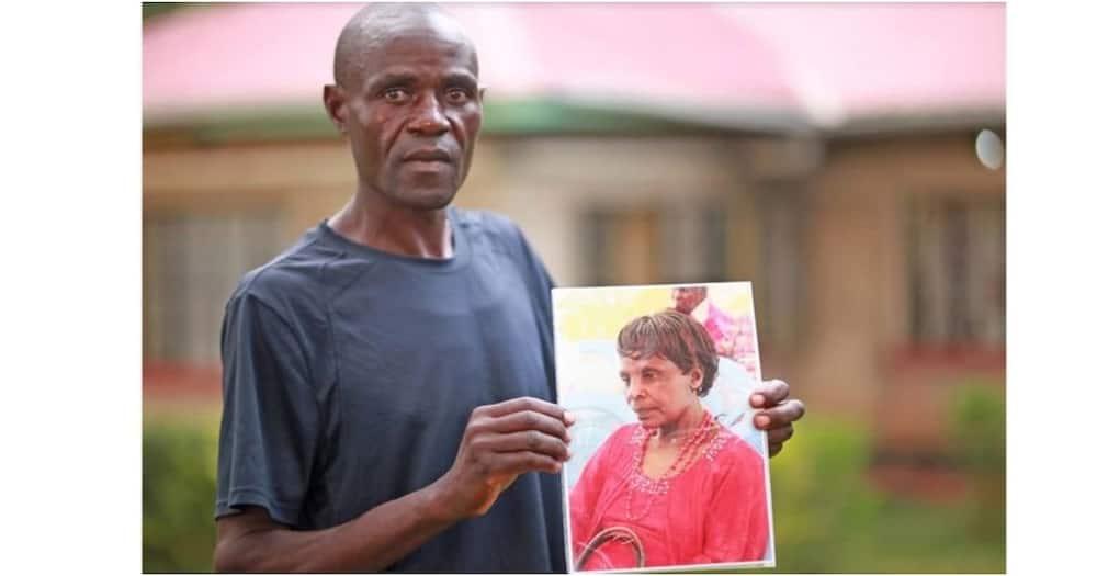 Benson Muhanji holds a portrait of his employer Benedina Nabwangu who was found murdered in her house. Photo: Nation