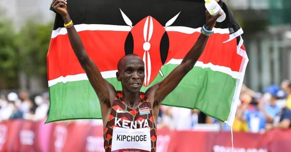 Eliud Kipchoge celebrates with the Kenyan national flag after winning the men's marathon at the Tokyo Olympics on Aug. 8, 2021, in Sapporo, northern Japan. (Photo by Kyodo News via Getty Images)