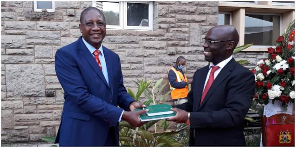 Prof Mwangi Iribe who led the team of experts receiving copies from Arap Kirui who lead the Parliamentary Team. Photo: National Assembly.